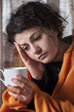 Ills of season. Woman with flu symptoms holding a cup in his hand Royalty Free Stock Image
