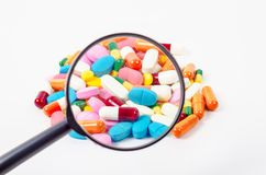 Ills under magnifying glass. Pills under magnifying glass on white background Stock Photos