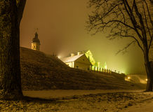 Illuminate castle framed by trees covered with snow and tree bra Royalty Free Stock Photo