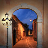 Illuminated alleyway with arched gate and lantern Royalty Free Stock Images