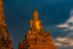 Illuminated ancient Buddha statue against cloudy sky on the back Royalty Free Stock Photo