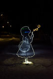 Illuminated angel figure at Christmas night. Illuminated the figure of a little girl blowing soap balls in Christmas Park at night Royalty Free Stock Images