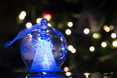 Illuminated angel figure in glass bulb, soft boke christmas ligh. Ts as background, Christmas decoration stock photography