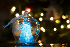 Illuminated angel figure in glass bulb, soft boke christmas ligh. Ts as background, Christmas decoration royalty free stock images
