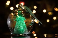 Illuminated angel figure in glass bulb, soft boke christmas ligh. Ts as background, Christmas decoration stock images