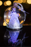 Illuminated angel figure in glass bulb, soft boke christmas ligh. Ts as background, Christmas decoration royalty free stock image