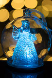 Illuminated angel figure in glass bulb, soft boke christmas ligh. Ts as background, Christmas decoration royalty free stock photo