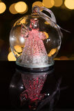 Illuminated angel figure in glass bulb, soft boke christmas ligh. Ts as background, Christmas decoration royalty free stock photography