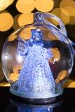 Illuminated angel figure in glass bulb, soft boke christmas ligh. Ts as background, Christmas decoration stock photo