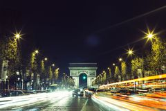 Illuminated Arc de Triomphe and the avenue Champs-Elysees in Paris. Famous touristic places and transportation concept. Night urban landscape with street Royalty Free Stock Photos