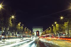 Illuminated Arc de Triomphe and the avenue Champs-Elysees in Paris. Famous touristic places and transportation concept Royalty Free Stock Photo