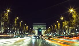Illuminated Arc de Triomphe and the avenue Champs-Elysees in Paris. Famous touristic places and transportation concept. Night urban landscape with street Stock Photos