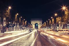 Illuminated Arc de Triomphe and the avenue Champs-Elysees in Paris. Famous touristic places and transportation concept. Night urban landscape with street Stock Image
