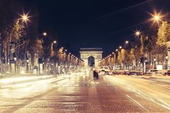Illuminated Arc de Triomphe and the avenue Champs-Elysees in Paris. Famous touristic places and transportation concept. Night urban landscape with street Stock Photo