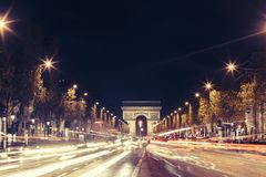 Illuminated Arc de Triomphe and the avenue Champs-Elysees in Paris. Famous touristic places and transportation concept. Night urban landscape with street Stock Photography