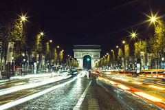 Illuminated Arc de Triomphe and the avenue Champs-Elysees in Paris. Famous touristic places and transportation concept. Night urban landscape with street Royalty Free Stock Photo