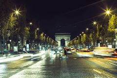 Illuminated Arc de Triomphe and the avenue Champs-Elysees in Paris. Famous touristic places and transportation concept. Night urban landscape with street Stock Images