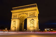 Illuminated Arc de Triomphe with light rails of passing traffic in Paris Royalty Free Stock Photo