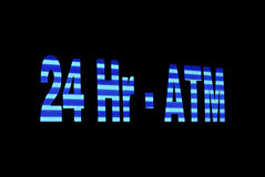 Illuminated ATM Sign. Blue stripped 24 Hr-ATM sign lit up after hours at night Stock Photo