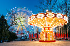 Illuminated Attraction Ferris Wheel And Carousel Merry-go-round. Rotating Illuminated Attraction Ferris Wheel And Carousel Merry-go-round On Summer Evening In Stock Images
