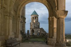 Illuminated Bagrati bell-tower through arch. Illuminated Bagrati Cathedral bell-tower through arch. Georgia, Kutaisi. Arch columns decoration is seen well Stock Images