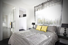 Illuminated bedroom with a pattern designed bed sheet Stock Photography