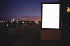 Illuminated blank billboard with copy space for your text message or content, public information board with night city on backgrou Royalty Free Stock Images
