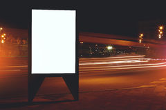 Illuminated blank billboard with copy space for your text message or content, public information board with shutter speed on backg Stock Photos