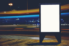 Illuminated blank billboard with copy space for your text message or promotional content, advertising mock up banner on roadside i royalty free stock photos