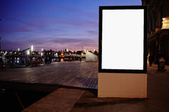 Illuminated blank billboard with copy space for your text message or promotional content,public information board against sunset s Royalty Free Stock Photos