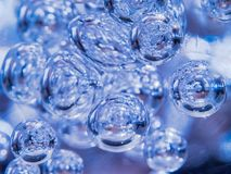 Illuminated Blue Bubbles Floating in Clear Liquid. Abstract Background Texture. Space, Ecology, Environment, Clean Sea, Potable. Water Concept royalty free stock photography