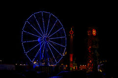Illuminated Blue Ferris Wheel at Night. A summer festival to celebrate July 4th, Independence Day, sets up temporary rides such as this blue ferris wheel that is Royalty Free Stock Images