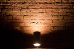 Illuminated by a brick wall in the dark Stock Images