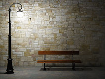 Illuminated brick wall with street light and bench Stock Images