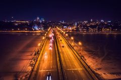 Illuminated bridge with car traffic on night city background, aerial view stock images