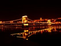Illuminated Bridge over River at Night Royalty Free Stock Photos