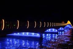 Illuminated bridge over river at night. Scenic view of colorful illuminated bridge reflecting on river at night Royalty Free Stock Photo