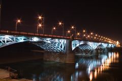 Illuminated bridge over Vistula River. Illuminated bridge piers over Vistula River by night (Warsaw, Poland Royalty Free Stock Photography