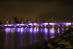 Illuminated Bridge over Water at Night Stock Photography