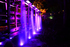 Illuminated Bridge and Waterfall. A waterfall cascades over an illuminated bridge with a Japanese style pagoda in the background Royalty Free Stock Image