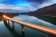 Illuminated bridge way over a lake Royalty Free Stock Photo