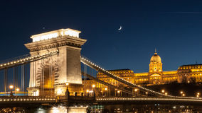 Illuminated Buda Castle and detailed view of Chain Bridge over Danube River in Budapest by night, Hungary Stock Photos