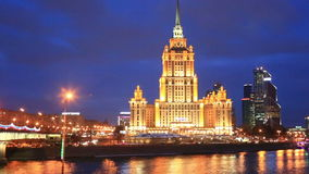 Illuminated building of Hotel Ukraina and Moscow river at night stock footage