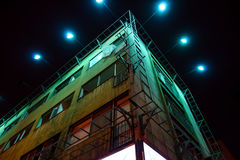 Illuminated building at night. Illuminated corner building at night with green tones by light type Royalty Free Stock Photography