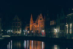 Illuminated Buildings by Canal at Night in Bruges Stock Photography