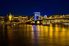 Illuminated buildings and Chain bridge at night in Budapest. Royalty Free Stock Photo