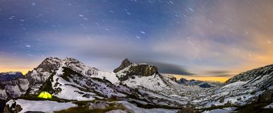 Panaorma of illuminated tent under starry night sky in snowy alpine mountains. Alps, Switzerland. Illuminated camping tent with star trails at night. High Stock Photos