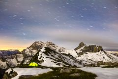 Tent glows under a starry night sky in snowy alpine mountains. Alps, Switzerland. Illuminated camping tent with star trails at night. High altitude alpine Royalty Free Stock Photos
