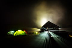 Illuminated camping tents at night in alpin zone. Illuminated camping tents at  foggy night in alpin zone Stock Photography