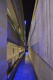 Illuminated Car Park Path at Night. A path running behind an illuminated concrete multi-storey car park at night Royalty Free Stock Photos